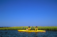 Two women in tandem kayak navigating through marsh grass along Cape Cod National Seashore, Eastham, Cape Cod