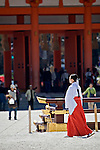 Girl in traditional Shinto shrine maiden dress, or miko hakama, walks in Heian-Jingu Shrine