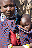 A Masai woman and her baby in a village near the Serengeti National Park, Tanzania. She is wearing the traditional ornately beaded necklaces and earrings.