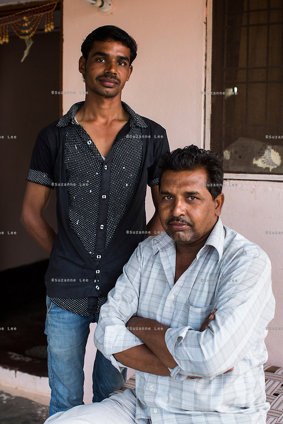 (L-R) Nitin Jat, 20, and his father Chetan Jat, 42, pose for a portrait in their home in Maheshwar, Khargone, Madhya Pradesh, India on 13 November 2014. Nitin, wants to continue doing Fairtrade cotton farming like the generations before him, but would like to also have a government job in the village so he can have an added source of income and pension (as did his grandfather). Photo by Suzanne Lee for Fairtrade