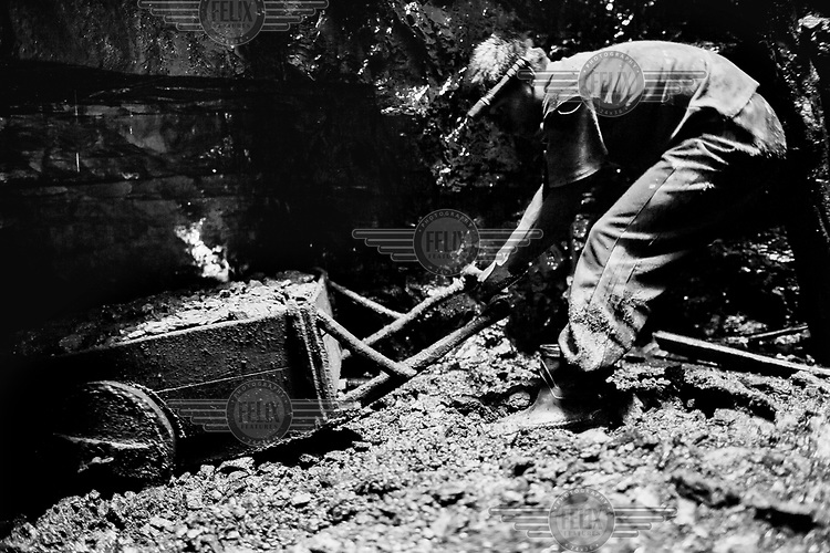 A miner pulls a cart full of coal, hacked from narrow shafts called 'rat holes' that radiate out from a central vertical shaft that extends from the surface. The miners must fill a large crane bucket before its raised to the surface. The miners work from 7am to 1pm and from 2pm to 7pm and sometimes later. They are paid for each full bucket and the money divided between all those working. There are approximately 5,000 privately owned coal mines in the region sitting on top of about 40 million tons of coal. Many use children, often trafficked, to work them under conditions that are hard and unregulated. The coal is dug out using primitive methods and basic tools.