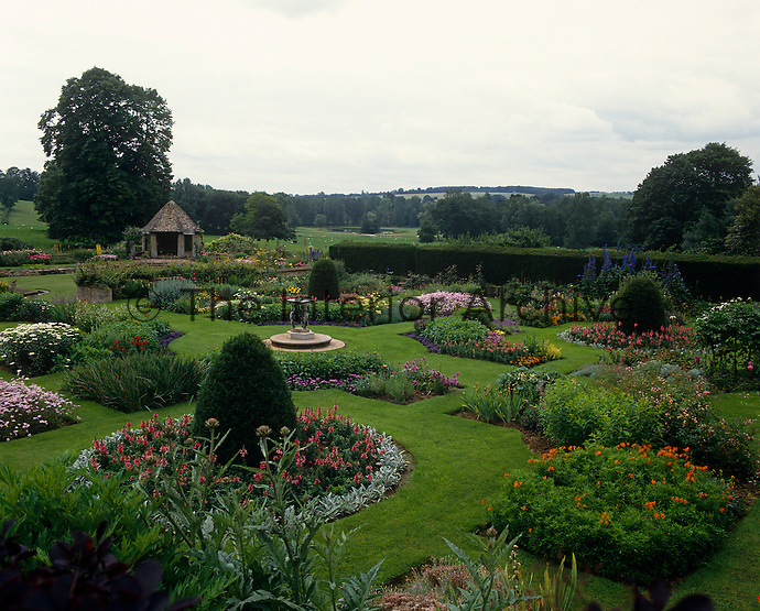 A beautifully manicured country house garden with an abundance of flowering shrubs and perennials