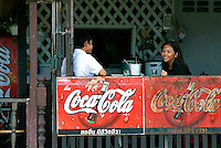 "A young couple sit at a resturant above a Coka-Cola sign along the Chao Phraya River in Bangkok. Once known as ""the Venice of the east,"" Bangkok can at times feel like a traditional Thai village struggling to retain its warmth and spirit as it quickly transforms into a modern concrete jungle."