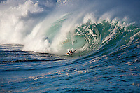 Body boarder riding a big hollow wave at Waimea Shorebreak, North Shore, Oahu, Hawaii