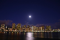 The city lights of Honolulu glow bright as a full-moon rises from behind.