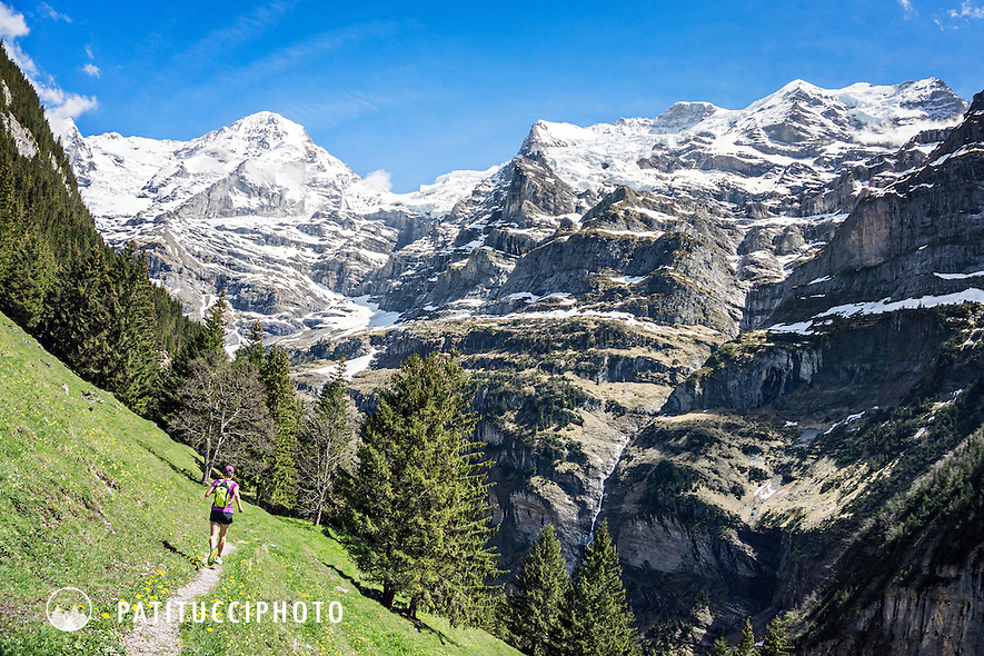 One woman trail running on the Trummelbach Falls Trail from Lauterbrunnen to Wengen, Switzerland, with views of the Jungfrau above.