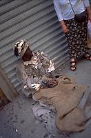 Homeless beggar age 38 in rags sitting on sidewalk.  New York New York USA