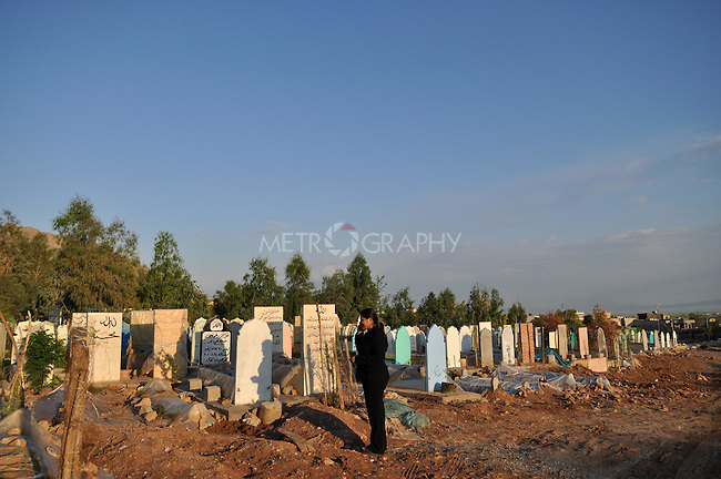 RANYA, IRAQ: A journalist in Ranya visits a cemetary where nameless women and girls who are not claimed by their families are buried.  Women and girls who are killed or commit suicide for honor related violene are viewed as bringing shame to their families. Even in death their families disown them.