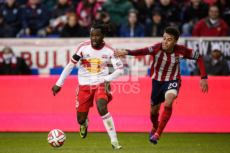 Peguy Luyindula (8) of the New York Red Bulls is defended by Carlos Alvarez (20) of Chivas USA. The New York Red Bulls and Chivas USA played to a 1-1 tie during a Major League Soccer (MLS) match at Red Bull Arena in Harrison, NJ, on March 30, 2014.