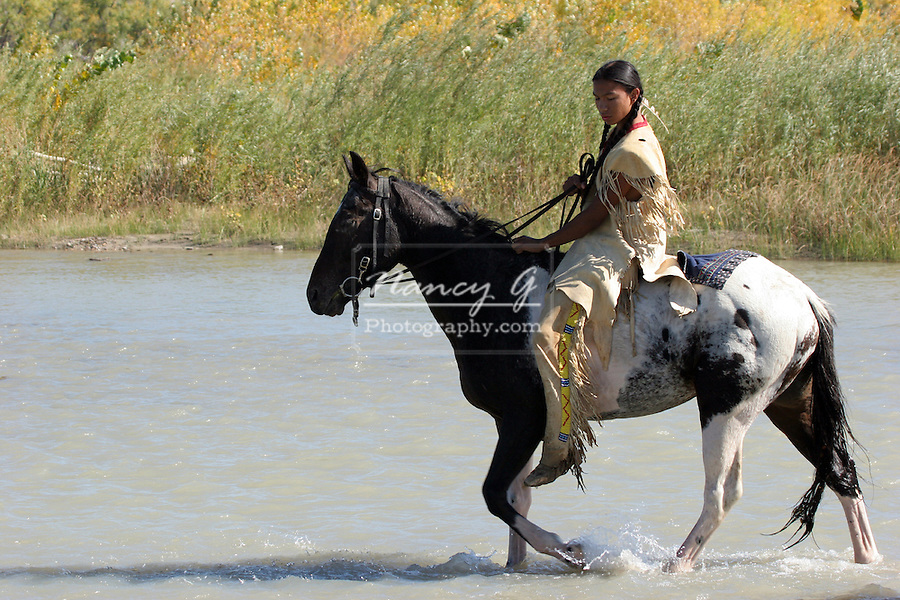 A young teenage Native American Indian boy riding an Indian pony in a river in South Dakota on the Reservation