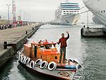 CAIRO, EGYPT - NOVEMBER 29: Egyptian man on a small boat near large cruise ships near Cairo, Egypt on November 29, 2007.
