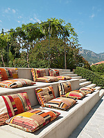 Colourful cushions are placed on stone steps beside a swimming pool providing a sunny spot to sit and relax.