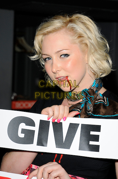 VICTORIA HART.Bloodlust Photocall to promote the forthcoming Bloodlust Ball and to promote the Blood Donor scheme, at Vendome, Piccadilly, London, England, UK..October 15th 2008.full length holding Give Blood sign slogan blood neckerchief mouth open nail varnish polish pink .CAP/CAN.©Can Nguyen/Capital Pictures.
