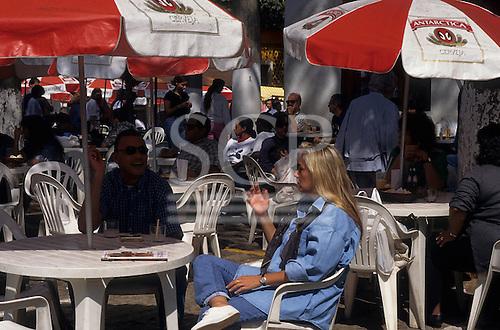 Sao Paulo, Brazil. Affluent couple enjoying a caipirinha coctail at a table outside at a sports club.