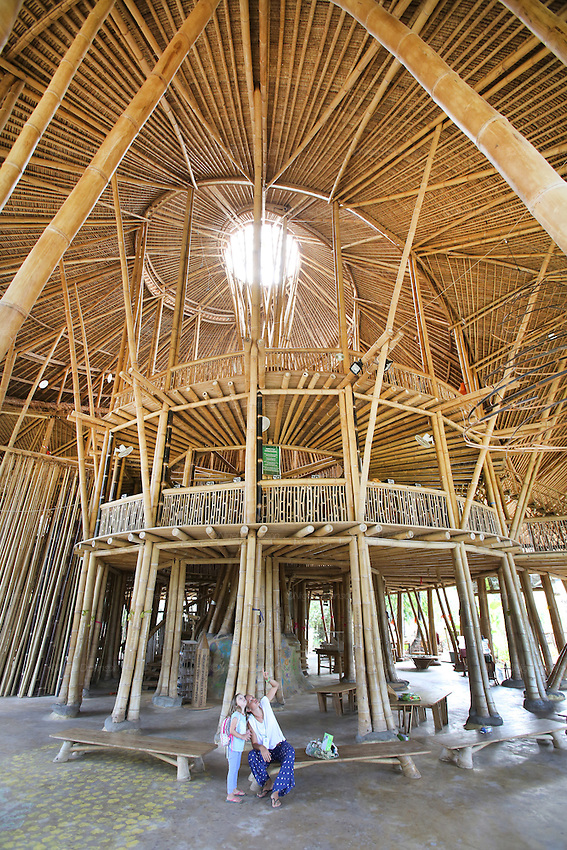"""""""Heart of School"""" Cathedral like bamboo architecture construction<br /><br />The Green School (Bali) is one of a kind in Indonesia. It is a private, kindergarten to secondary International school located along the Ayung River near Ubud, Bali, Indonesia. The school buildings are of ecologically-sustainable design made primarily of bamboo, also using local grass and mud walls. There are over 600 students coming from over 40 countries with a percentage of scholarships for local Indonesian students.<br /><br />The impressive three-domed """"Heart of School Building"""" is 60 metres long and uses 2500 bamboo poles. The school also utilizes renewable building materials for some of its other needs, and almost everything, even the desks, chairs, some of the clothes and football goal posts are made of bamboo.<br /><br />The educational focus is on ecological sustainability. Subjects taught include English, mathematics and science, including ecology, the environment and sustainability, as well as the creative arts, global perspectives and environmental management. This educational establishment is unlike other international schools in Indonesia. <br /><br />Renewable energy sources, including solar power and hydroelectric vortex, provide over 50% of the energy needs of the school. The school has an organic permaculture system and prepares students to become stewards of the environment. <br /><br />The school was founded by John and Cynthia Hardy in 2008."""