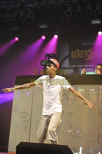Wiz Khalifa (Cameron Jibril Thomaz) performing live at V Festival Hylands Park, Chelmsford, England..20th August 2011.stage concert live gig performance music half length white t-shirt sunglasses shades baseball cap hat arm in air tattoos beige jeans denim arms.CAP/BEL.©Tom Belcher/Capital Pictures.