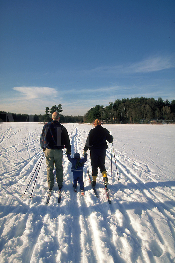 Parents hold their toddler's hands while cross-country skiing.