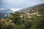 A woman hiking along a path in Corsica, France, stops for a moment to admire a village across the valley.