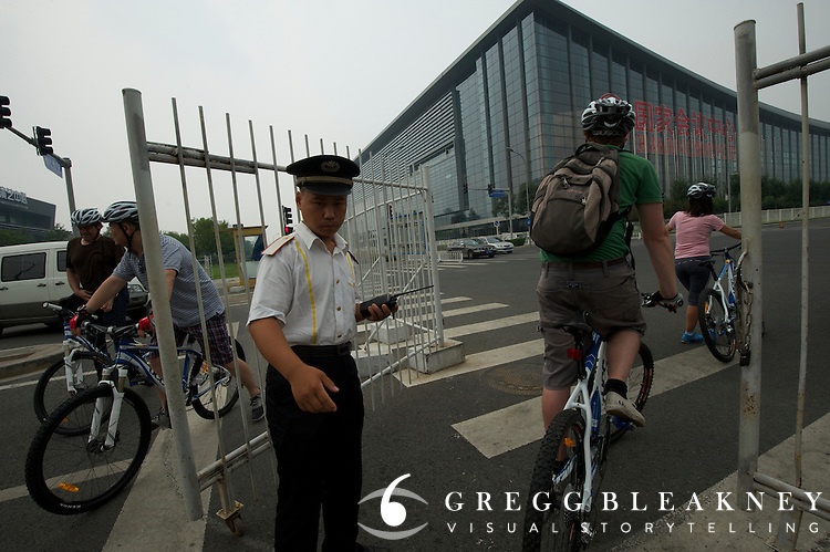 Security official opens the gate for delegates - 2011 Tour of Beijing Scouting Photos - Stage 1 Time Trial, Beijing, China