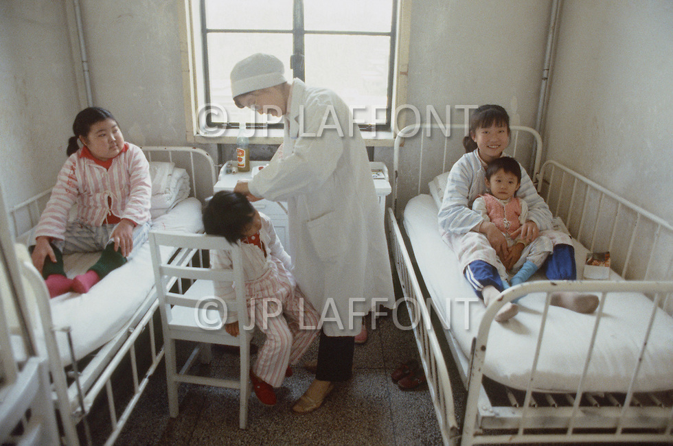 October 1984. Near Beijing, at the Children Hospital. Nurses taking care of kids. Kid receiving treatment from a nurse.