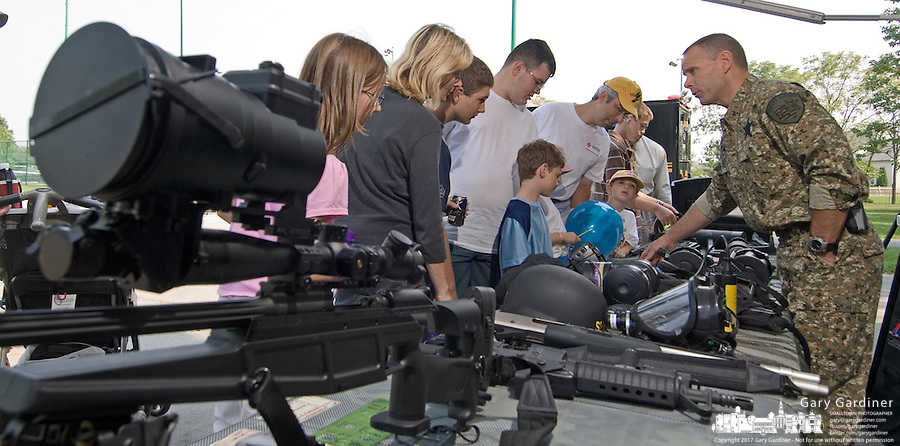 A Franklin County Ohio SWAT officertalks about the team's weapons with a group of kids and their parents at the Cops and Kids Day at Hoff Woods Park in Westerville, Ohio.<br />
