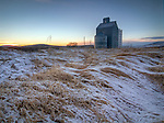Idaho, Palouse, Moscow. A grain elevator and snow covered waves of grass at sunset on the Palouse in winter.