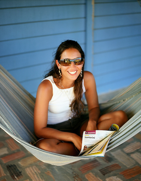 CABURE, BRAZIL : A young Brazilian woman relaxes in a hammock at Hotel Pousada Do Buriti. The Porto Buriti is located at the beach of Cabure, an ecological paradise among the Lencois Maranhenses, at the edge of the river Rio Preguicas and the Atlantic Ocean. It is neighboring the villages of Mandacaru and Atins. Cabure, Brazil.