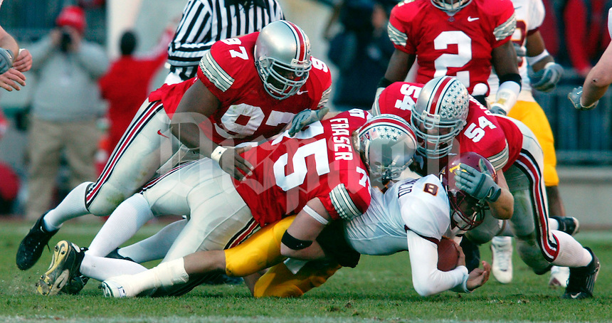 Ohio State's Simon Fraser, 75, sacks Minnesota's quarterback Asad Abdul Khaliq, 8, for a loss of 3 yards in the first quarter of thier game at The Ohio Stadium, November 2, 2002. Teammates Kenny Peterson, 97 and Tim Anderson, 54, help in the play. (Dispatch photo by Neal C. Lauron)