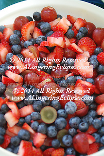 Summer harvest of fresh fruits: strawberry, blueberry and red grape in a white serving bowl.