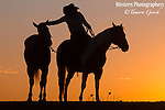 A photograph of a cowgirl on her horse leaning over and petting the horse she is ponying.  Silhouette image. Cowboy Photos, riding,roping,horseback