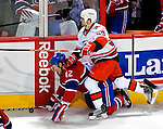 31 March 2010: Montreal Canadiens center Dominic Moore is checked to the ice by Carolina Hurricanes right wing forward Chad LaRose in the first period at the Bell Centre in Montreal, Quebec, Canada. The Hurricanes defeated the Canadiens 2-1 in their last meeting of the regular season. Mandatory Credit: Ed Wolfstein Photo