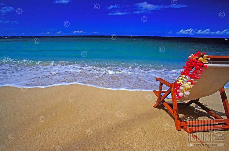 Beach chair draped with a colorful plumeria flower lei on a sunny tropical Hawaiian white sand beach