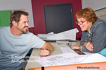 One young man 30+ and one young woman 40+ talk and laugh about drawing project in landscape architectural design class