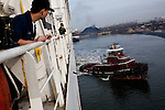 Sailors watch as a tugboat tows the USNS Comfort, a naval hospital ship, out from port as it gets under way to Haiti to assist earthquake victims on Saturday, January 16, 2010 in Baltimore, MD.