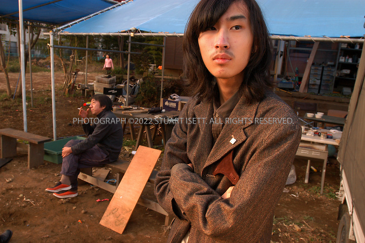 11/29/2002--Shiki City, Japan..19 year old Dai Hasebe at 'Ayutaka', a free space created by Nobuyuki Minami (sitting behind) for children who are bullied in school or are shut-ins . Dai has been a 'hikikomori', or shut-in, since he was 11, rarely venturing out of his family's apartment, instead spending all his time shut off from the world in the tiny apartment. Dai makes models to help keep himself busy..Experts estimate that at up to a million Japanese live as shut-ins as they hide from the social pressures of Japanese .All photographs ©2003 Stuart Isett.All rights reserved.This image may not be reproduced without expressed written permission from Stuart Isett.