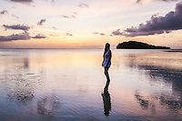 Young woman ankle deep in Guam lagoon sunset.