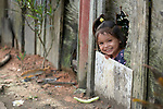 An indigenous girl looks through a hole in a fence in the Nacoes Indigenas neighborhood in Manaus, Brazil. The neighborhood is home to members of more than a dozen indigenous groups, many of whose members have migrated to the city in recent years from their homes in the Amazon forest.