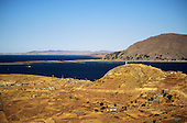 Lake Titicaca, Peru. View of the lake with a small arid village and a white cross on top of a hillock.