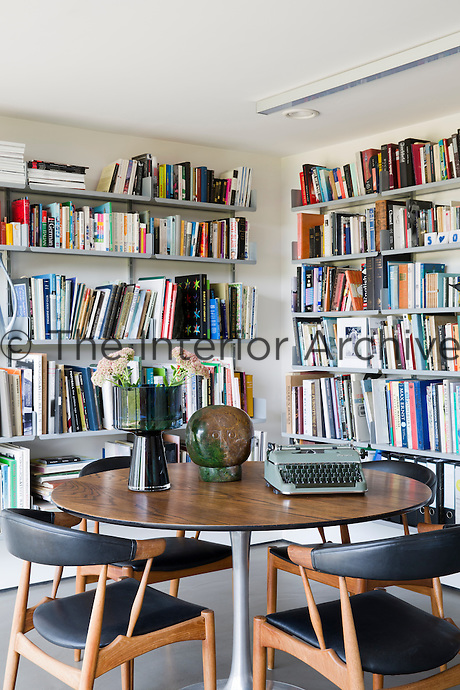 The library serves as an additional home office, complementing a separate study and design studio. The shelving is a classic Dieter Rams design. The chairs are mid-century Danish pieces. The table is vintage Eero Saarinen and the sculpted head on it is by Henry Munyaradzi.