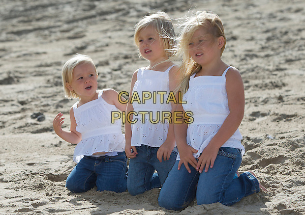 PRINCESS ARIANE, PRINCESS ALEXIA & PRINCESS CATHARINA-AMALIA OF THE NETHERLANDS.The Crown Prince of the Netherlands and his family take part in a photoshoot at the beach of Wassenaar, the Netherlands, 20th July 2009..half length royals royal dutch Princess of Orange-Nassau sand white tops matching sisters children kids Holland kneeling down.CAP/PPG/JH.©Jens Hartmann/People Picture/Capital Pictures