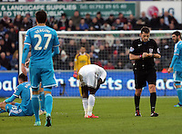 SWANSEA, WALES - FEBRUARY 07: Match referee Phil Dowd (R) is booking Nathan Dyer of Swansea (C) for his foul against Anthony Reveillere of Sunderland (L) during the Premier League match between Swansea City and Sunderland AFC at Liberty Stadium on February 7, 2015 in Swansea, Wales.