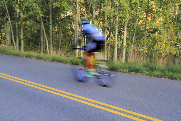 Bike racer blurred due to high speed, Maroon Bells Valley Road, near Aspen, Colorado, USA John offers fall foliage photo tours throughout Colorado.