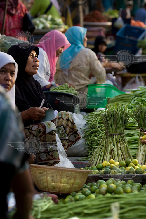 Women at their fruit and vegetable stalls at a market in Pattani.