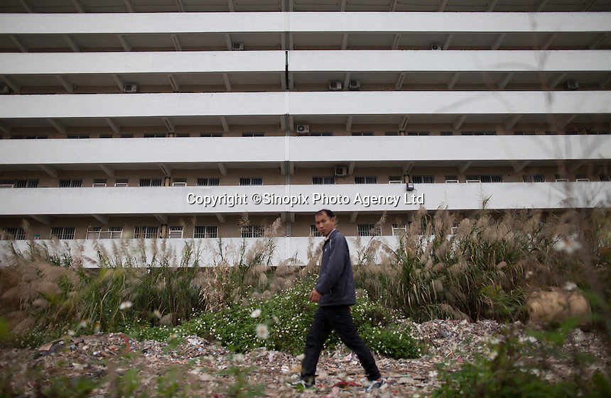 A man walks past a Yue Yuen Industrial Holdings Limited factory dormitory building in Dongguan, Guangdong Province, China, 03 March 2015.