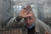 """Vasiliy<br /><br />Portraitserie von Obdachlosen in Kiew während der Corona Pandemie. Der Fotograf hat sie gebeten sich hinter dem Glas der Bahnhöfe fotografieren zu lassen. Er sagt: Ich porträtierte die Obdachlosen hinter dem Glas der Haltestellen und Unterführungen - das sind die Orte, an denen sie übernachten und leben. Das Glas ist aber auch symbolisch wie eine Wand zwischen uns und ihnen - wir sehen sie, aber wir hören sie nicht, sie sind wie Fische in Aquarien - isoliert von der Gesellschaft. Es ist nicht möglich, durch das Glas eine helfende Hand zu erreichen. Wir sympathisieren mit ihnen, wenn wir Ihnen während der Quarantäne von unseren Fenstern aus zuschauen, aber wir sind durch unsere komfortablen Wohnungen geschützt und sie blicken von unten zu unseren Fenstern hoch. / Portrait series of homeless people in Kiev during the Corona Pandemic. The photographer asked them to be photographed behind the glass of the train stations. He says: """"I portrayed the homeless behind the glass of the stations and underpasses - these are the places where they stay and live. But the glass is also symbolic like a wall between us and them - we see them but we don't hear them, they are like fish in aquariums - isolated from society. It is not possible to reach a helping hand through the glass. We sympathize with them when we watch them from our windows during quarantine, but we are protected by our comfortable apartments and they look up to our windows from below."""