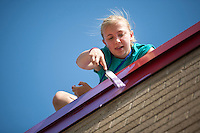 "Samantha Zent paints on the roof during ""Circle the City with Service,"" the Kiwanis Circle K International's 2015 Large Scale Service Project, on Wednesday, June 24, 2015, at the Friendship Westside Center for Excellence in Indianapolis. (Photo by James Brosher)"