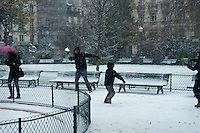Family throwing snowballs in a Paris park.