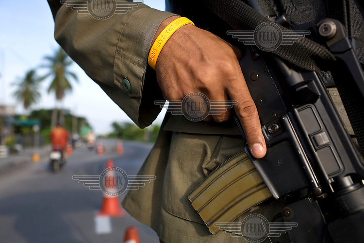 """An armed soldier wears a wristband with the inscription """"Long live the King"""" at one of the many checkpoints in and around the town of Pattani. The insurgency in Southern Thailand began as a conflict between the Malay muslim population and central government, but now the boundaries have become blurred and various guerilla groups have become involved. No-one seems certain as to who is fighting who. As of March 2008, the insurgency had claimed as many as 3,000 lives."""