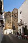 Narrow street cafe and church of Santa Maria de la Asuncion, Arcos de la Frontera, Cadiz province, Spain