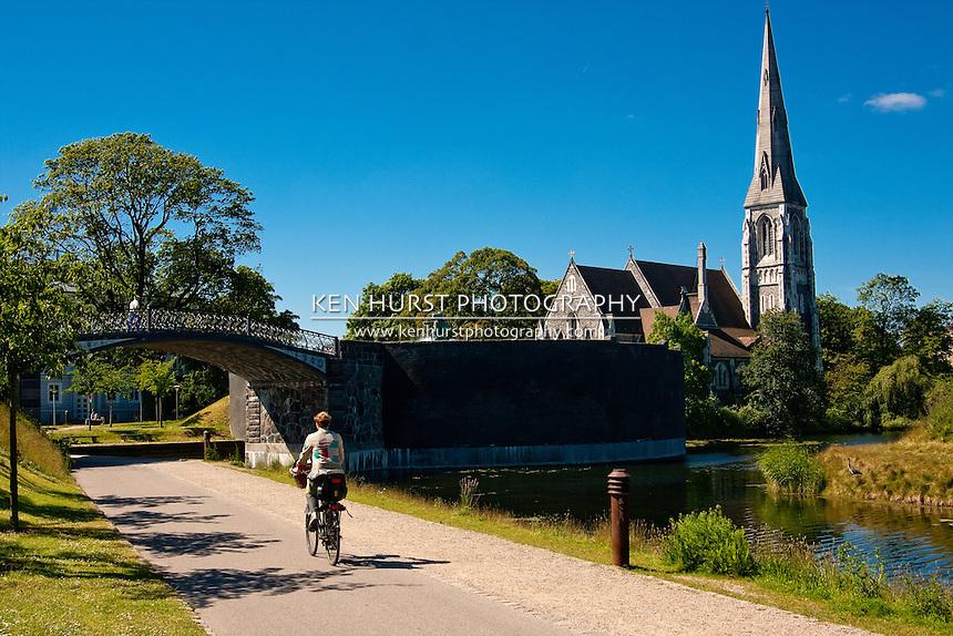 Bicyclist riding on a path near Saint Albans Anglican Church in Copenhagen, Denmark.